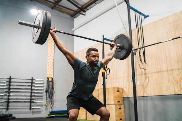 Portret młodego sportowca crossfit robi ćwiczenia ze sztangą