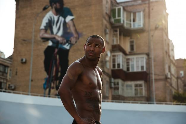 Portret młodego sportowca mięśni patrząc od hotelu
