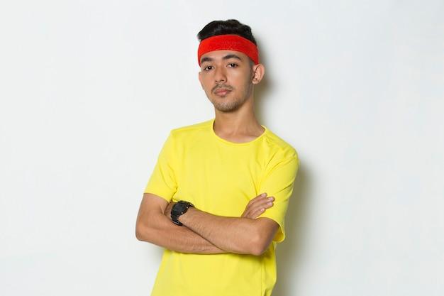 Portret młodego sportowca ubranego w żółtą koszulkę na białym tle