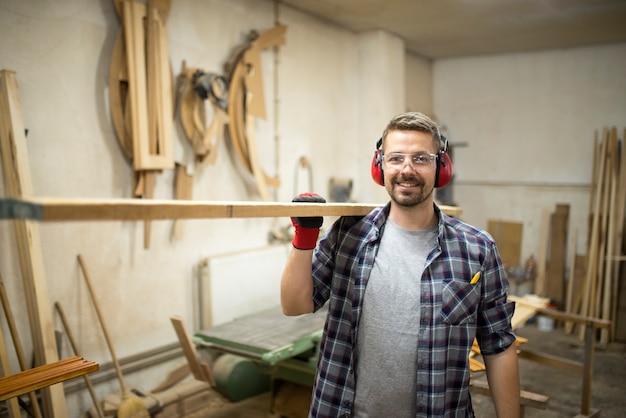Portret młodego stolarza trzymając drewno w swoim warsztacie stolarskim