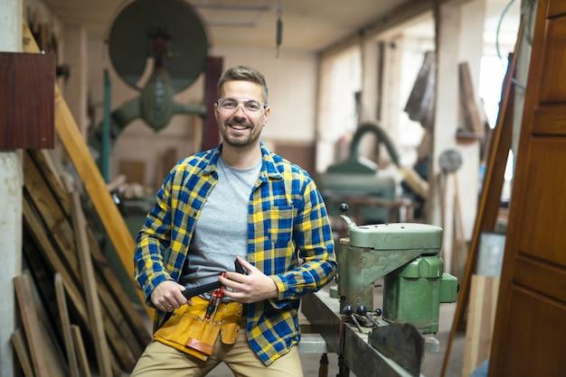 Portret młodego stolarza w jego warsztacie stolarskim