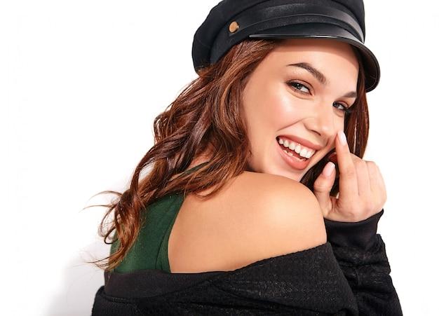 Portret młodego stylowego śmiejącego się modelu w czarnych letnich ubraniach w czapce z naturalnym makijażem na białym