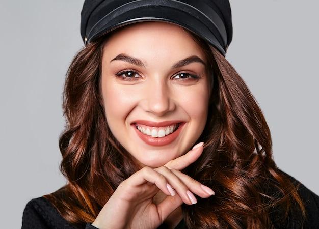Portret młodego stylowego śmiejącego się modelu w czarnych letnich ubraniach w czapce z naturalnym makijażem na szaro