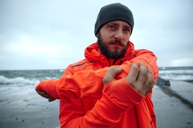 Portret młodego surowego bruneta z bujną brodą, rozgrzewającego się przed porannym biegiem nad morzem, patrząc w zamyśleniu przed siebie z założonymi ustami. męski model fitness