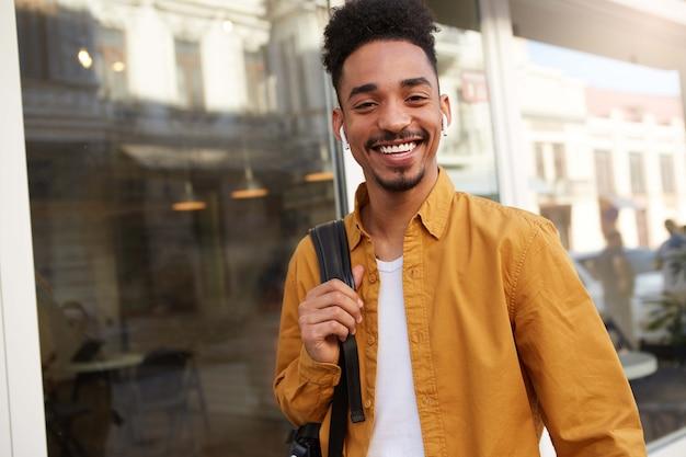 Portret młodego szczęśliwego ciemnoskórego faceta w żółtej koszuli idącego ulicą słuchając ulubionej piosenki na słuchawkach, wygląda wesoło, cieszy się słonecznym dniem w mieście i szeroko się uśmiecha.