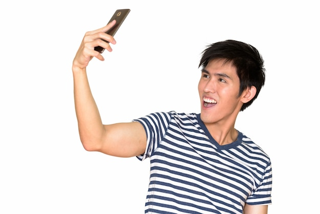 Portret młodego szczęśliwego człowieka azji biorąc selfie z telefonu komórkowego na białym tle białej ścianie