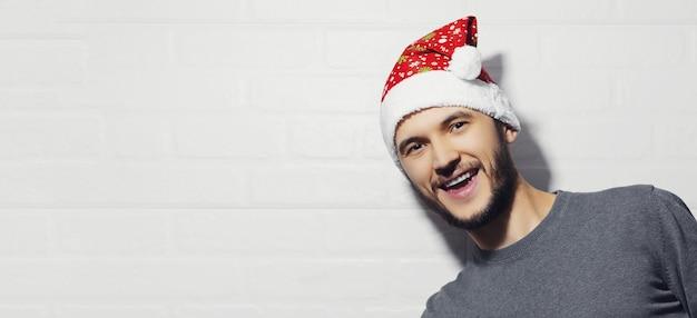 Portret młodego szczęśliwego człowieka z santa hat na tle białego ceglanego muru z miejsca na kopię. koncepcja bożego narodzenia.