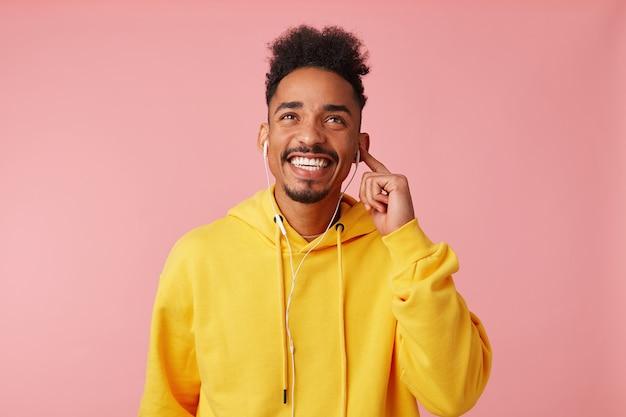 Portret młodego szczęśliwego faceta afroamerykanów w żółtej bluzie z kapturem, ciesząc się swoją ulubioną fajną piosenką na słuchawkach, marzycielsko patrząc w górę, stojąc i szeroko uśmiechając się.