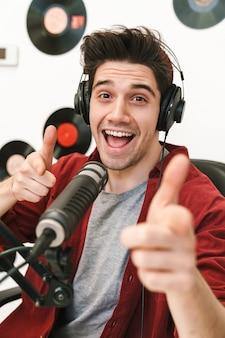 Portret młodego szczęśliwego kaukaskiego mężczyzny występującego w programie radiowym podczas nagrywania podcastu do programu online