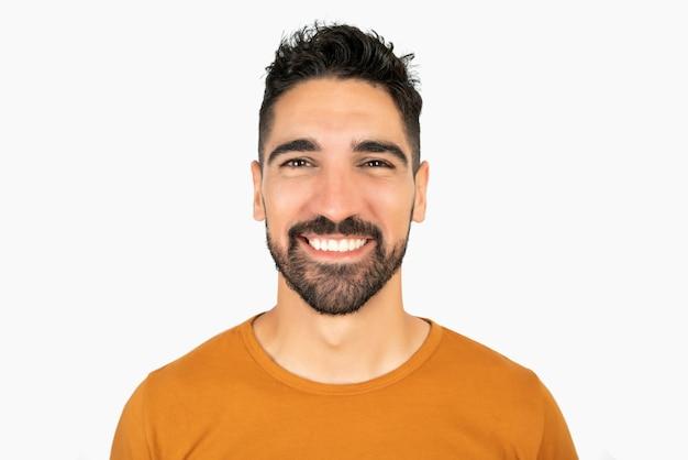 Portret młodego szczęśliwego mężczyzny uśmiecha się przeciw białej przestrzeni