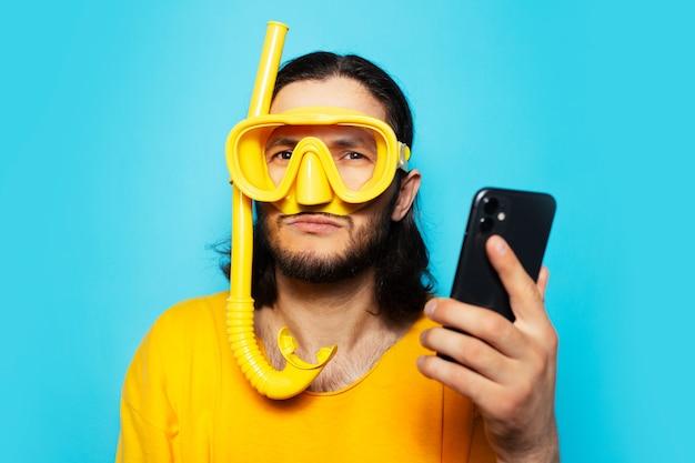 Portret młodego szczęśliwego mężczyzny w kolorze żółtym, noszącego sprzęt do nurkowania ze smartfonem w rękach