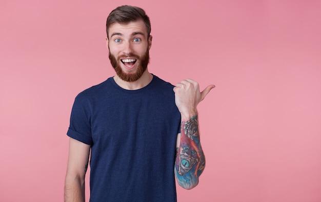 Portret młodego szczęśliwego, rudobrodego, młodego faceta z szeroko otwartymi ustami ze zdziwienia, ubrany w niebieską koszulkę, wskazujący palcem na skopiowanie miejsca po prawej stronie na różowym tle.
