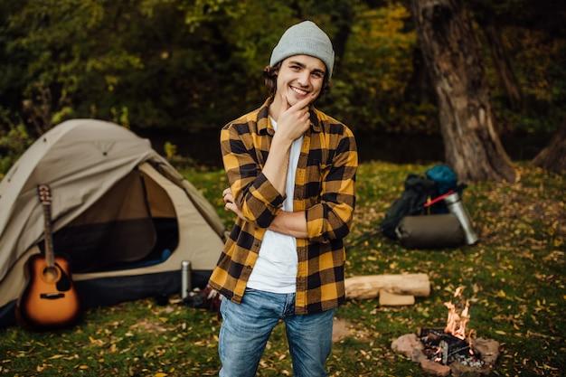 Portret młodego szczęśliwego uśmiechniętego mężczyzny stojącego obok namiotu