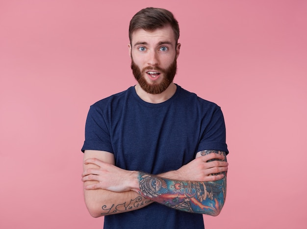 Portret młodego szczęśliwego zdumionego atrakcyjnego rudobrodego młodego faceta ze skrzyżowanymi rękami, na sobie niebieską koszulkę, patrząc w kamerę z szeroko otwartymi ustami ze zdziwienia na białym tle na różowym tle.