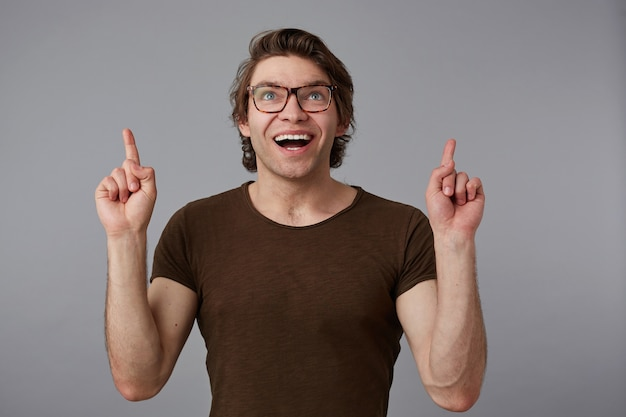 Portret młodego szczęśliwego zdumionego mężczyzny w okularach, stoi na szarym tle z zaskoczonym wyrazem, wskazuje palcami w górę na kopię miejsca nad głową.