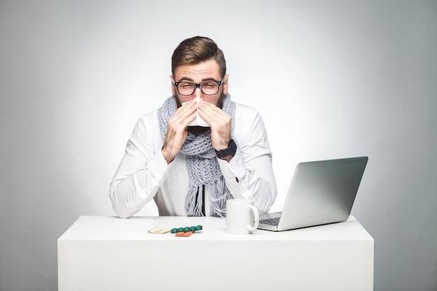 Portret młodego szefa chorego bazgroły w białej koszuli, szaliku i czarnym krawacie siedzi w biurze i musi skończyć ważny raport, ma wirusa grypy. strzał studio, na białym tle, szare tło, wewnątrz