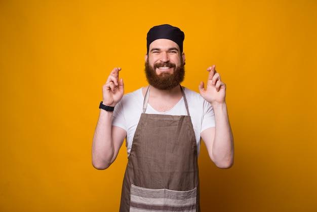 Portret młodego szefa kuchni mężczyzna z skrzyżowanymi palcami