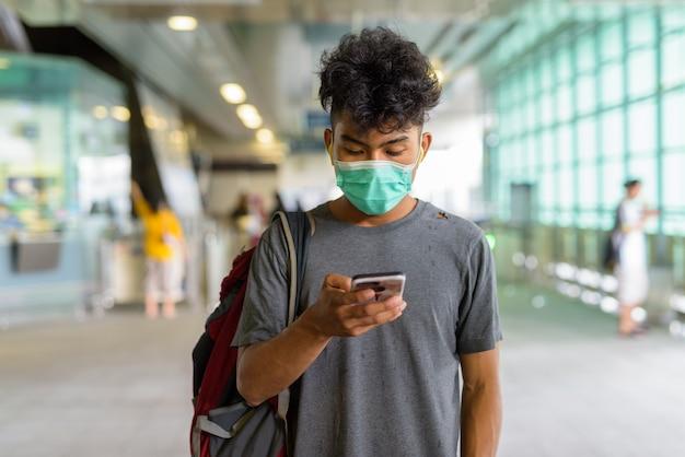 Portret młodego turysty z azji jako turysty z maską do ochrony przed wybuchem koronawirusa na stacji kolejowej na niebie