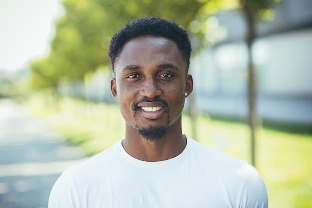 Portret młodego tysiącletniego afroamerykanina patrzącego na kamerę szczęśliwego i uśmiechniętego w białej koszulce