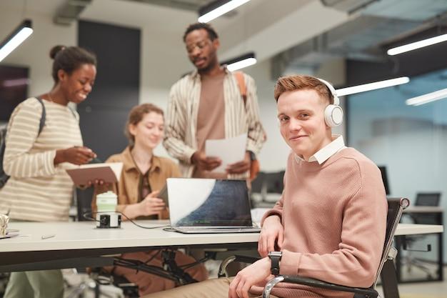 Portret młodego ucznia płci męskiej uśmiechającego się do kamery podczas korzystania z laptopa w szkolnej bibliotece, skopiuj miejsce