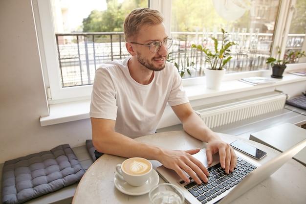 Portret młodego, uroczego faceta, pracującego zdalnie w miejskiej kawiarni, odwracającego wzrok z delikatnym uśmiechem, robiącej pauzę w pracy i myślącej o czymś pozytywnym