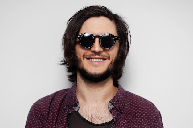Portret młodego uśmiechniętego faceta z okrągłymi okularami przeciwsłonecznymi.