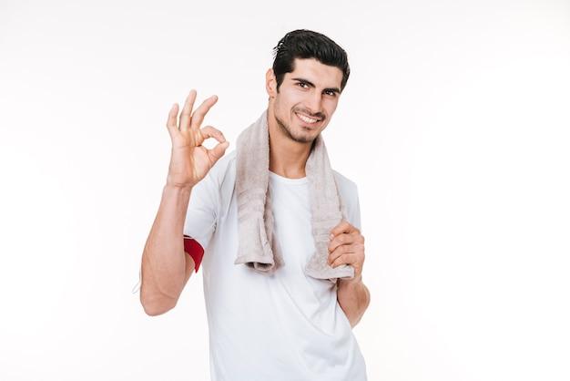 Portret młodego uśmiechniętego mężczyzny fitness z ręcznikiem pokazującym w porządku gest i patrząc na kamerę na białym tle na białym tle