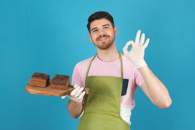 Portret młodego uśmiechniętego mężczyzny trzymającego plastry ciasta i wskazującego ok.