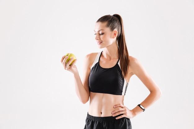 Portret młodego uśmiechniętego sportwoman gospodarstwa zielone jabłko