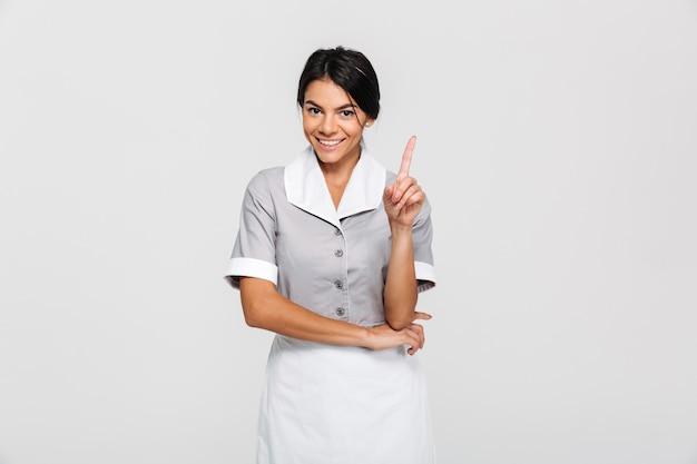 Portret młodego uśmiechniętej brunetki żeński cleaner wskazuje z palcem oddolnym podczas gdy stojący