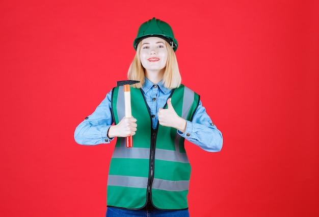 Portret młodego w mundurze i kasku sprawia, że kciuk gest trzymając młotek