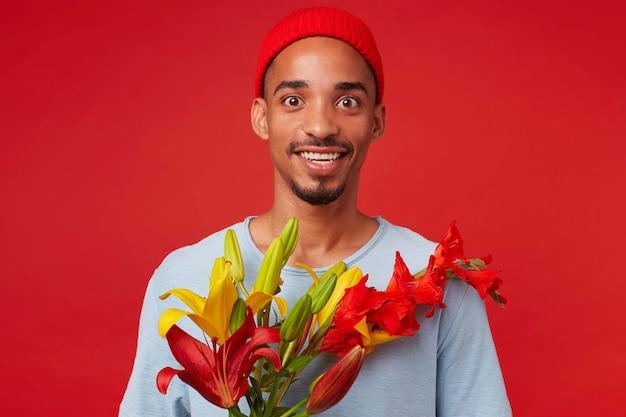 Portret młodego wesołego atrakcyjnego faceta w czerwonym kapeluszu i niebieskiej koszulce, trzyma bukiet w dłoniach, patrzy w kamerę z radosną miną i uśmiechnięty, stoi na czerwonym tle.