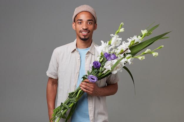 Portret młodego wesołego atrakcyjnego faceta w szarym kapeluszu, trzyma bukiet w dłoniach, patrzy w kamerę z wyrazem zadowolenia i uśmiechnięty, stoi na szarym tle.