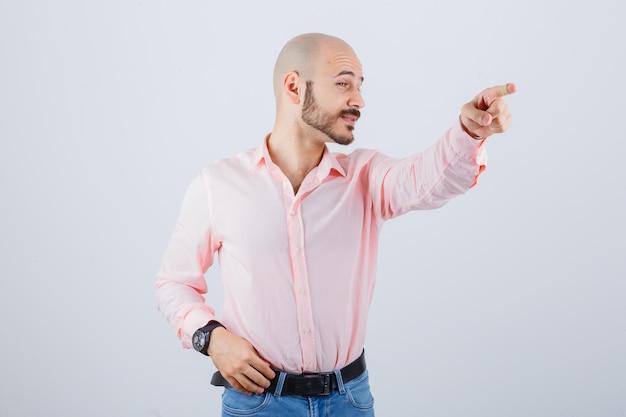 Portret młodego, wesołego mężczyzny, wskazującego od