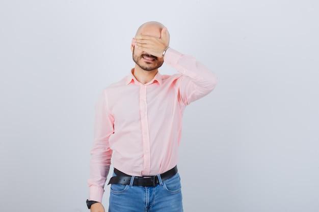 Portret młodego wesołego mężczyzny zakrywającego oczy