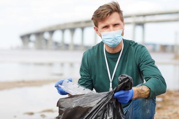 Portret młodego wolontariusza w masce ochronnej, wkładanie śmieci do torby i patrząc na kamery na zewnątrz