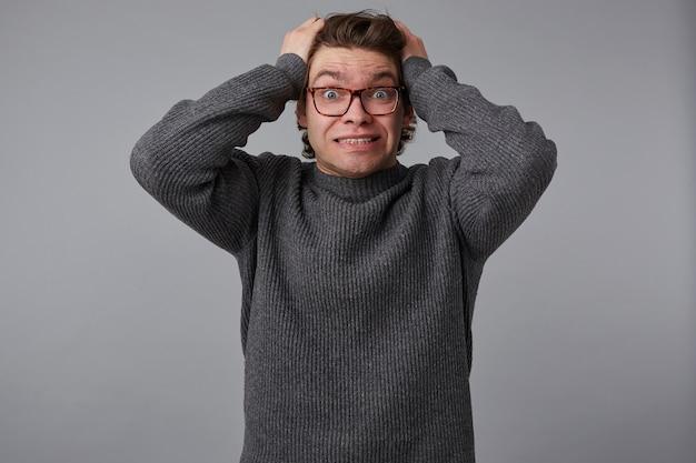 Portret młodego wstrząśniętego atrakcyjnego mężczyzny w okularach nosi szary sweter, stoi na szarym tle i raduje się, nie może powstrzymać emocji, trzyma głowę, patrzy w kamerę z szeroko otwartymi oczami.