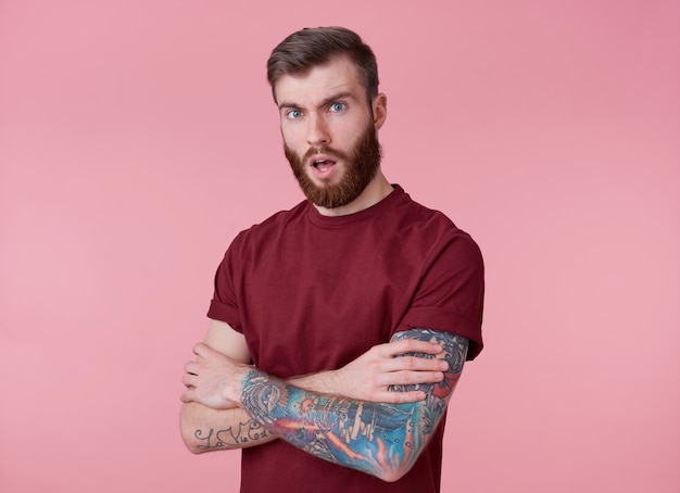 Portret młodego wytatuowanego brodatego mężczyzny z czerwonymi ustami w pustej koszulce, stoi ze skrzyżowanymi rękami na różowym tle, patrzy w kamerę z otwartymi ustami.