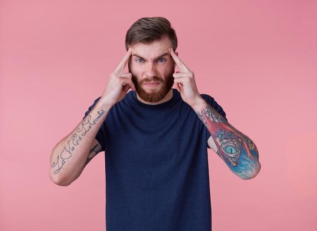 Portret młodego wytatuowanego, rudego brodacza w pustej koszulce, czuje ból głowy i dotyka skroni, stoi na różowym tle i marszczy brwi.