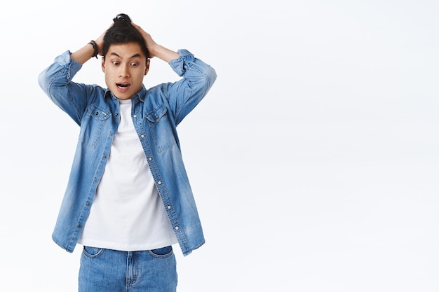 Portret młodego zakłopotanego azjatyckiego faceta czuje się zaniepokojony i panikuje, patrząc w dół zmartwiony i chwyta głowę, złamał kosztowną rzecz, stojąc zaniepokojony niezdecydowaną, białą ścianą