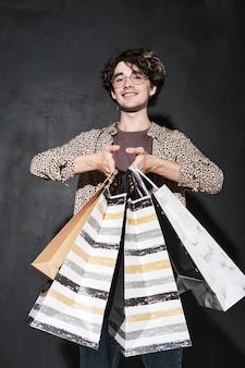 Portret młodego zakupoholiczki trzymającego torby na zakupy na czarnym tle