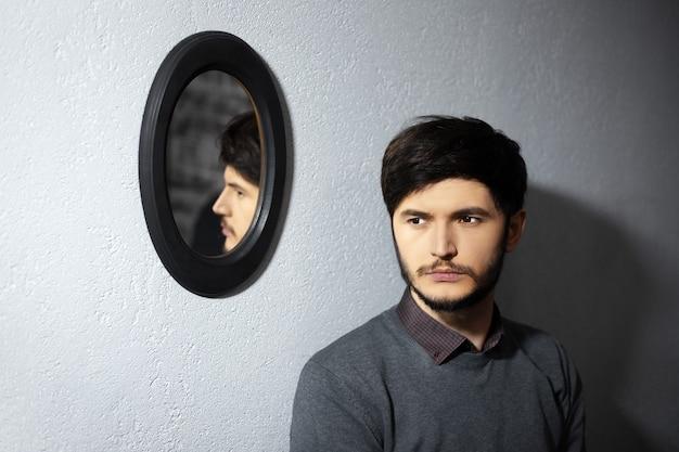 Portret młodego zamyślonego mężczyzny w pobliżu jego odbicia na owalnym czarnym lustrze