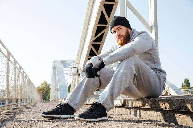 Portret młodego zamyślonego sportowca w stroju sportowym odpoczywającego po treningu na zewnątrz