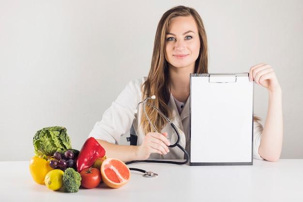Portret młodego żeńskiego dietician mienia pusty schowek w klinice