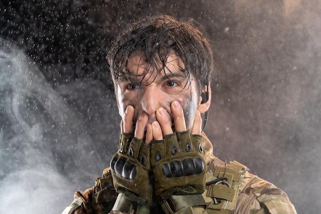 Portret młodego żołnierza w mundurze na ciemnej ścianie