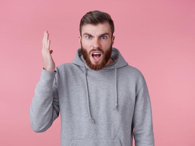 Portret młodego zszokowanego rudobrodego mężczyzny w szarej bluzie z kapturem, wygląda złowrogo i niezadowolony, z jedną uniesioną ręką przegrał swoją ulubioną drużynę. stoi na różowym tle i ma szeroko otwarte usta.