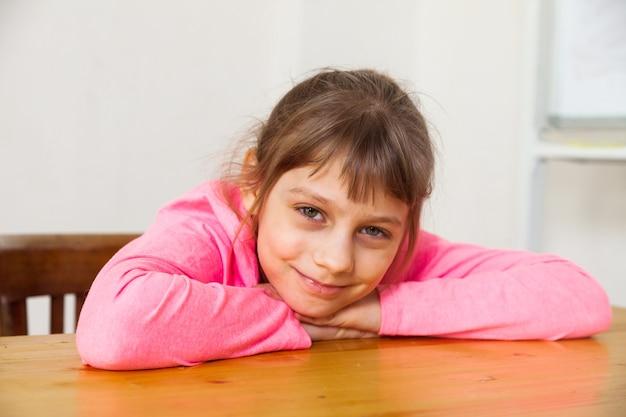 Portret młodej 8-letniej dziewczynki przed białą ścianą