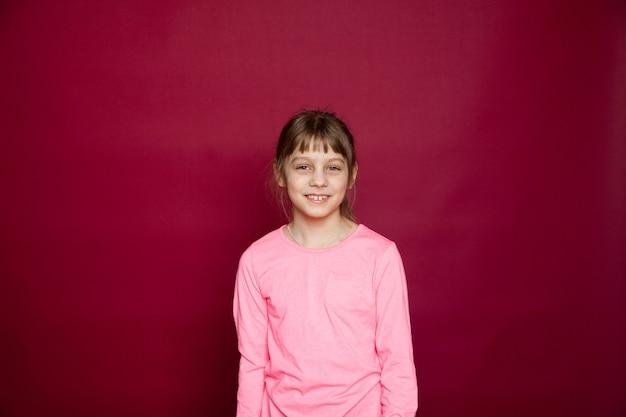 Portret młodej 8-letniej dziewczyny przed czerwoną ścianą w studio