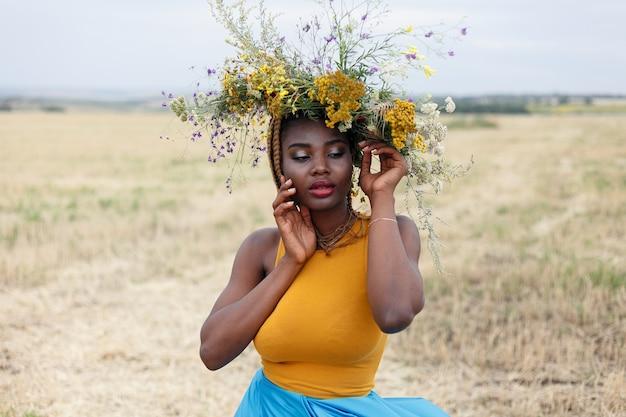 Portret młodej afroamerykanki, modelki, z dużymi kwiatami we włosach. portret dziewczynki w krzywym planie w polu z kwiatami. wieniec na głowę