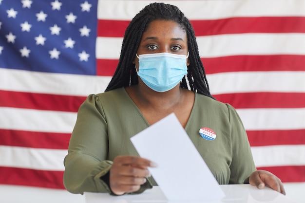 Portret młodej afroamerykanki noszącej maskę, umieszczając biuletyn głosowania w urnie i stojąc przed amerykańską flagą w dniu wyborów, skopiuj miejsce
